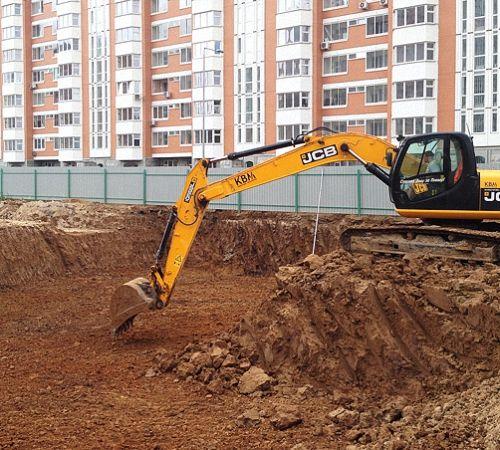 Расчистка участка под фундамент с использованием экскаватора.
