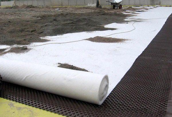 Укладка геотекстиля при возведении фундамента на болотистой местности.