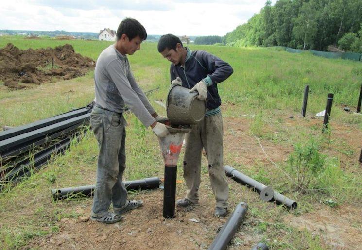Процесс ручного бетонирования полых свай после установки.