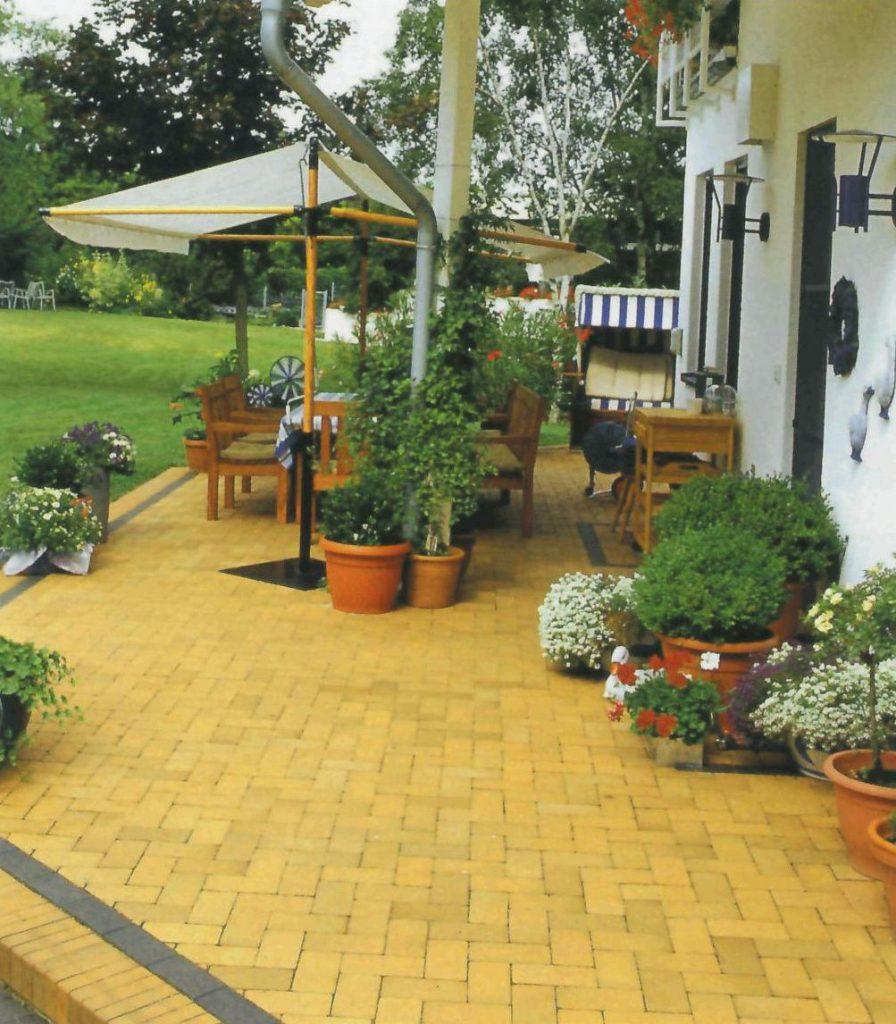 Желтый клинкерный камень брусчатки хорошо сочетается с зеленью сада.